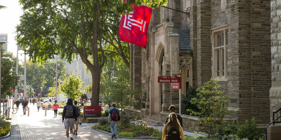 College students walk across campus on a sunny day with Temple University flag