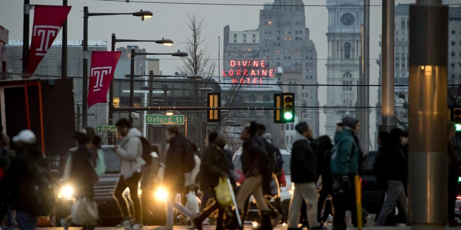 Students crossing Broad Street on Temple's Main Campus at dusk