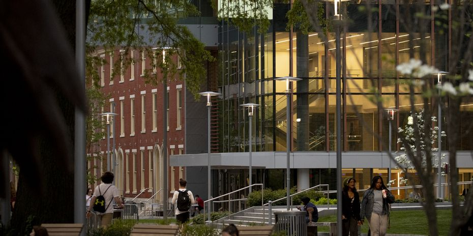 Students walking down Polett Walk in front of Charles library at dusk