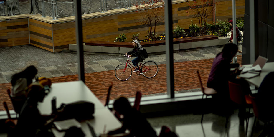 a female student riding her bike viewed from Charles Library.