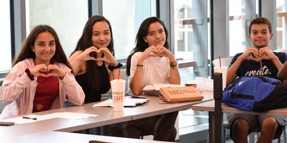 Group of male and female pre-college students sit together in a classroom and hold up their hands in the shape of hearts.
