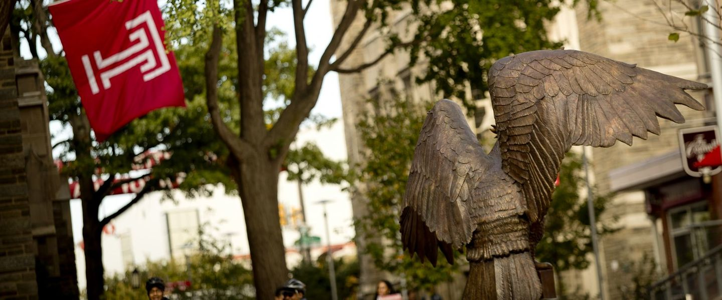 Trees in Lenfest Oconnor plaza with owl statue and Temple University flag