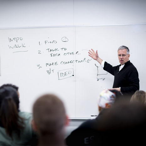 a professor stands at a white board