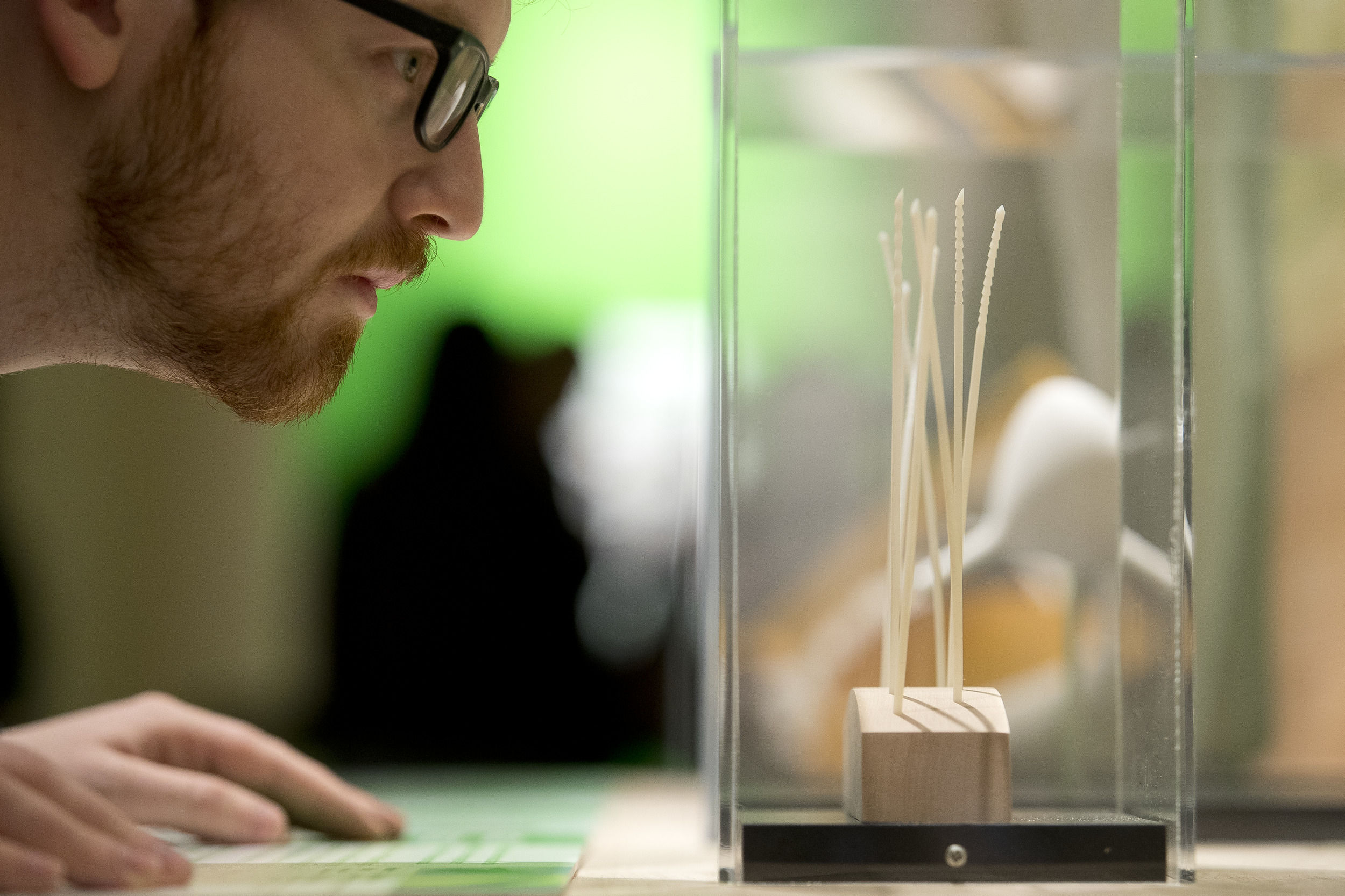 A student examines the 3D needles exhibit at the Charles Library.
