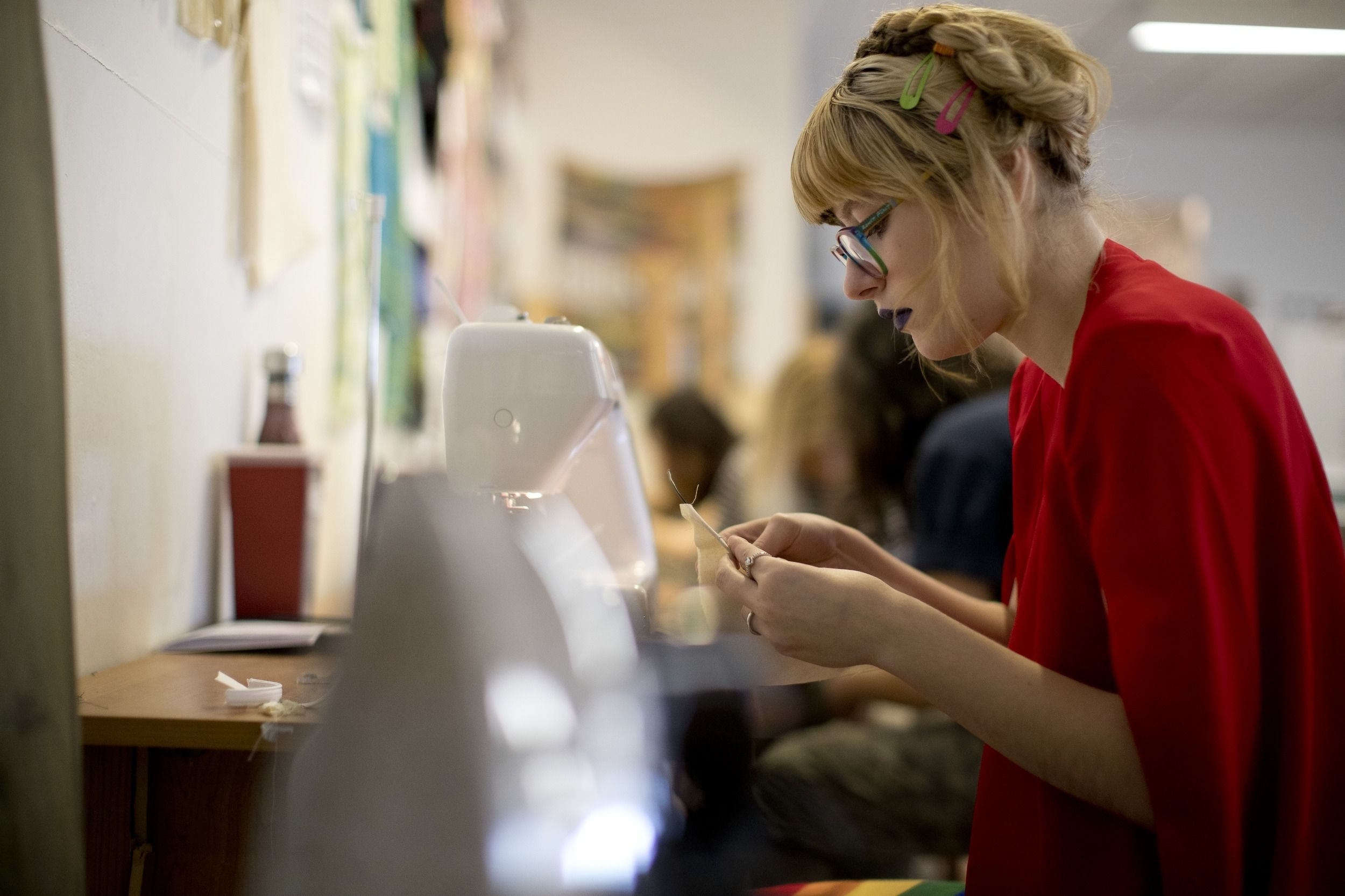A student works at a sewing machine during class.