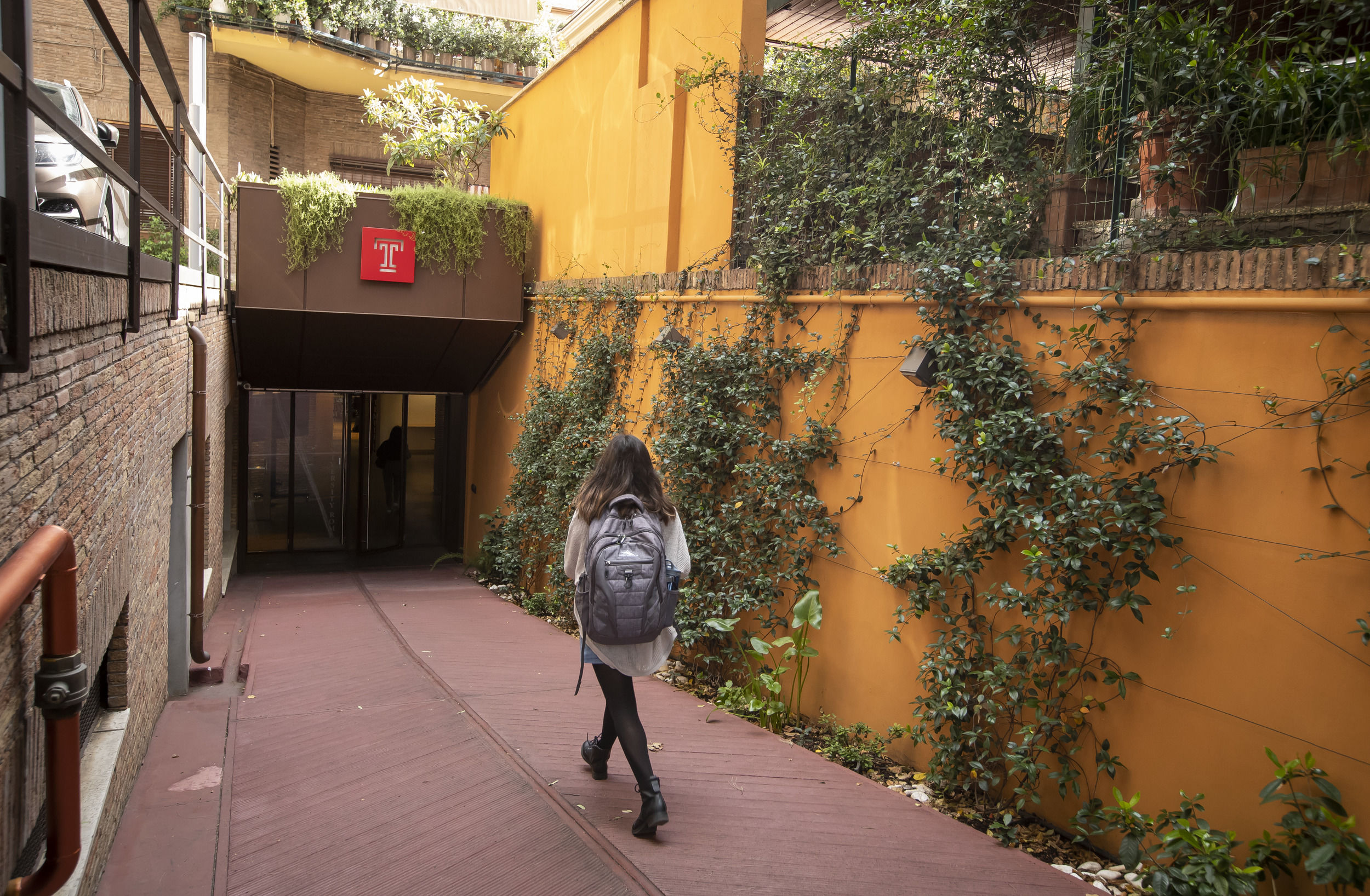 A student walking towards the entrance of a building on the Temple Rome campus.