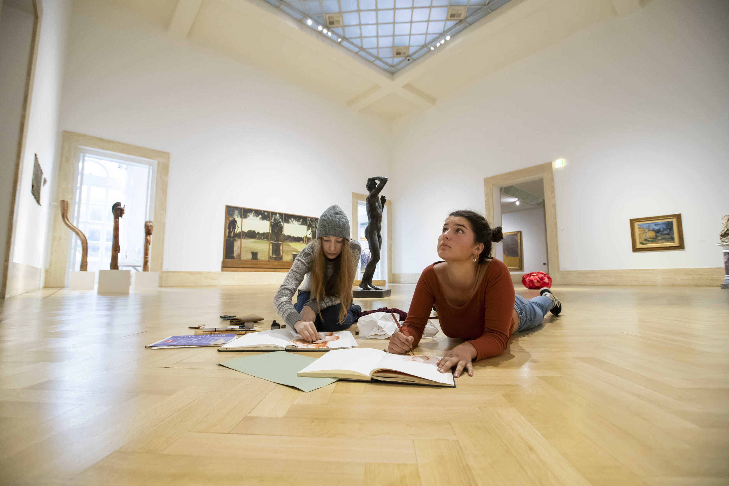 Two students laying on the floor of an art gallery in Rome, looking up at artwork.