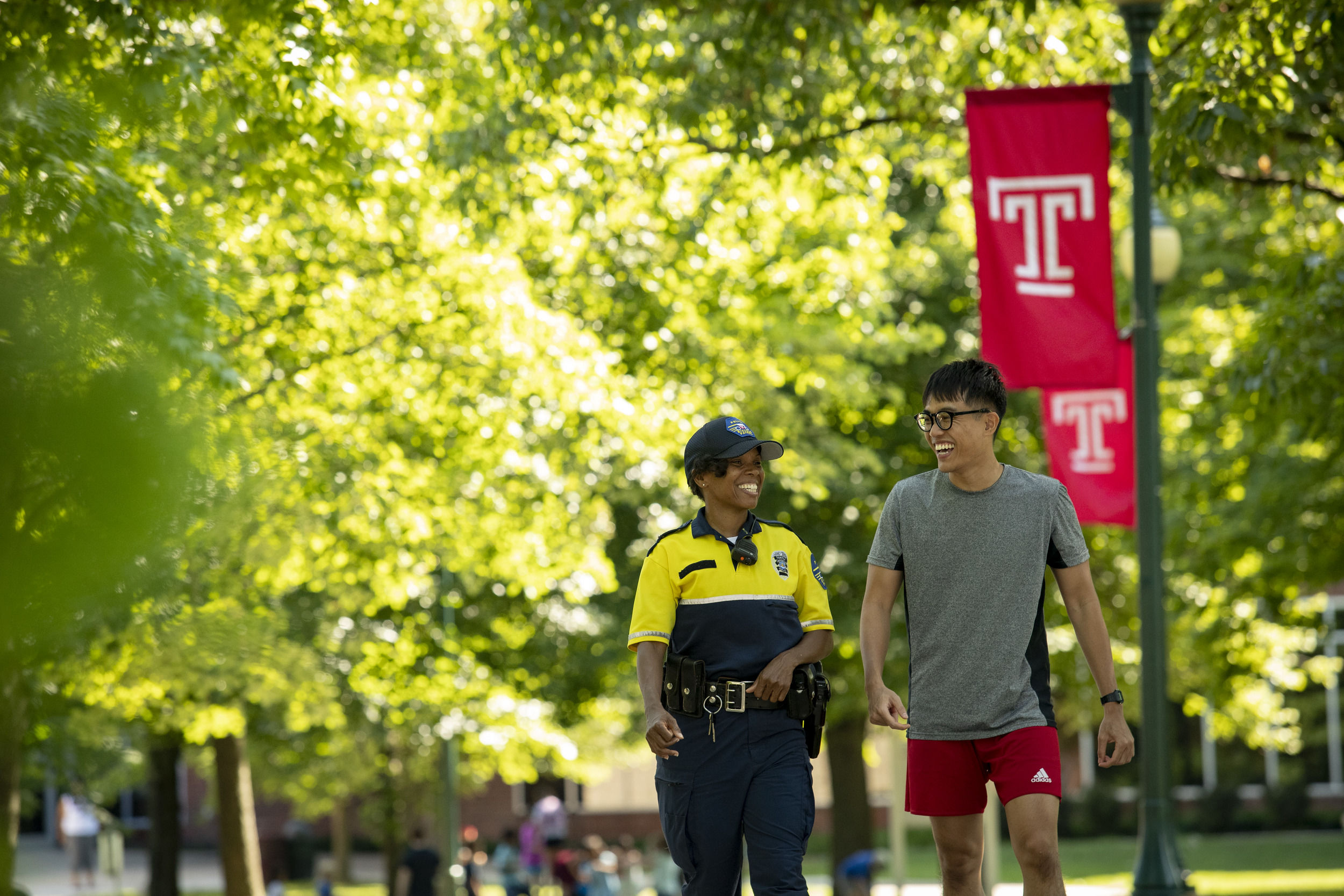 A student walking with Ambler Campus security.