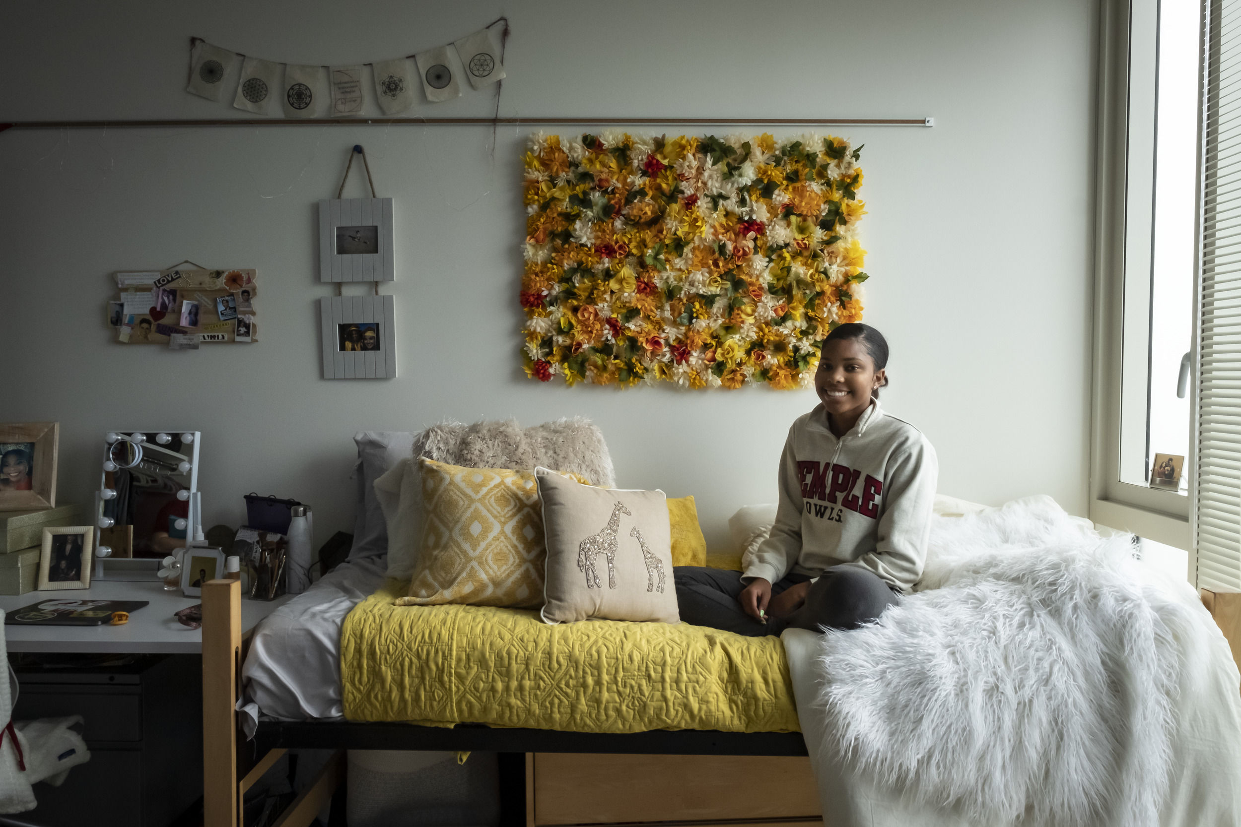 A student sits in their newly decorated room at Temple University.