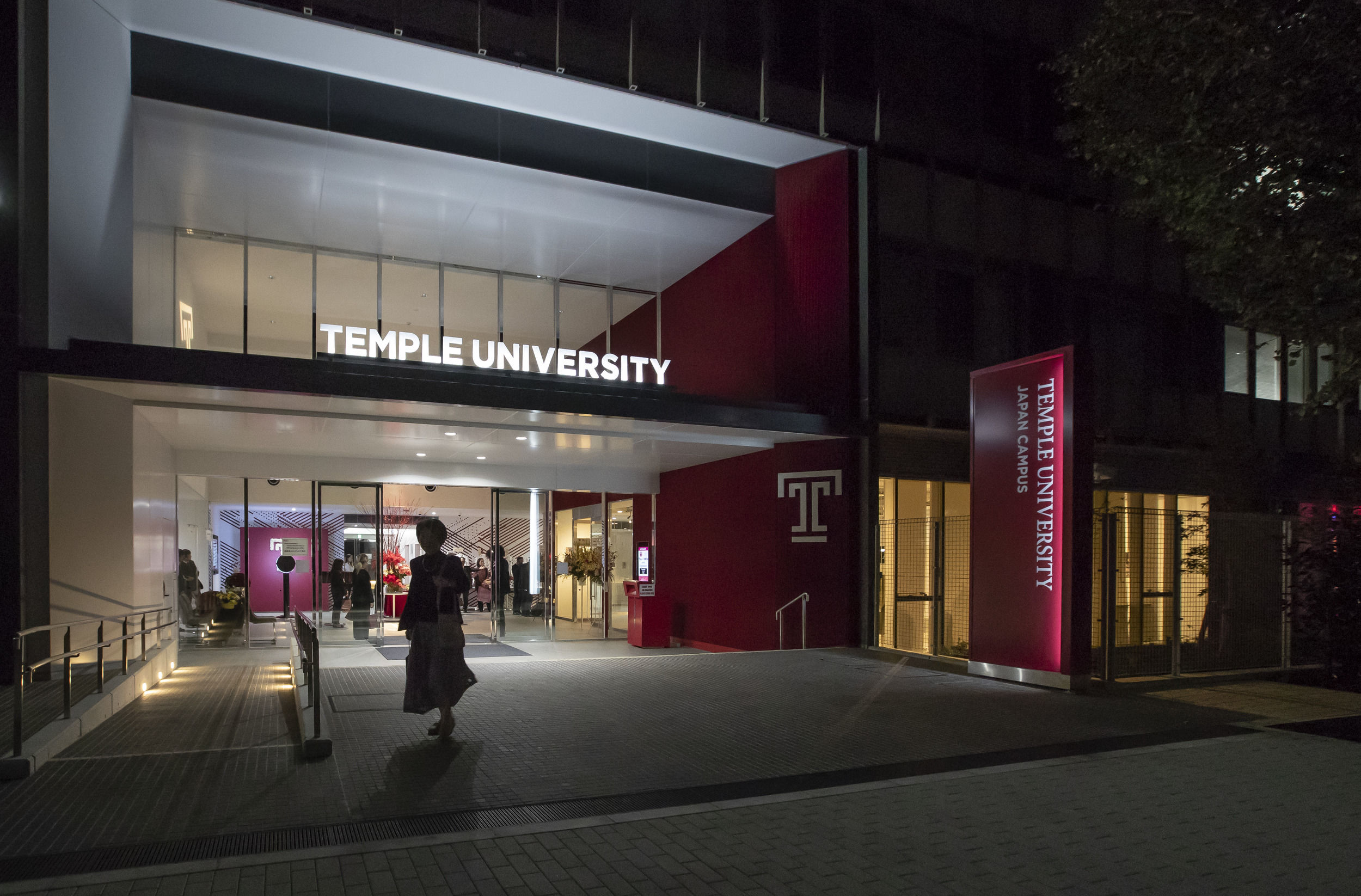 A student entering a building on Temple Japan campus at night.