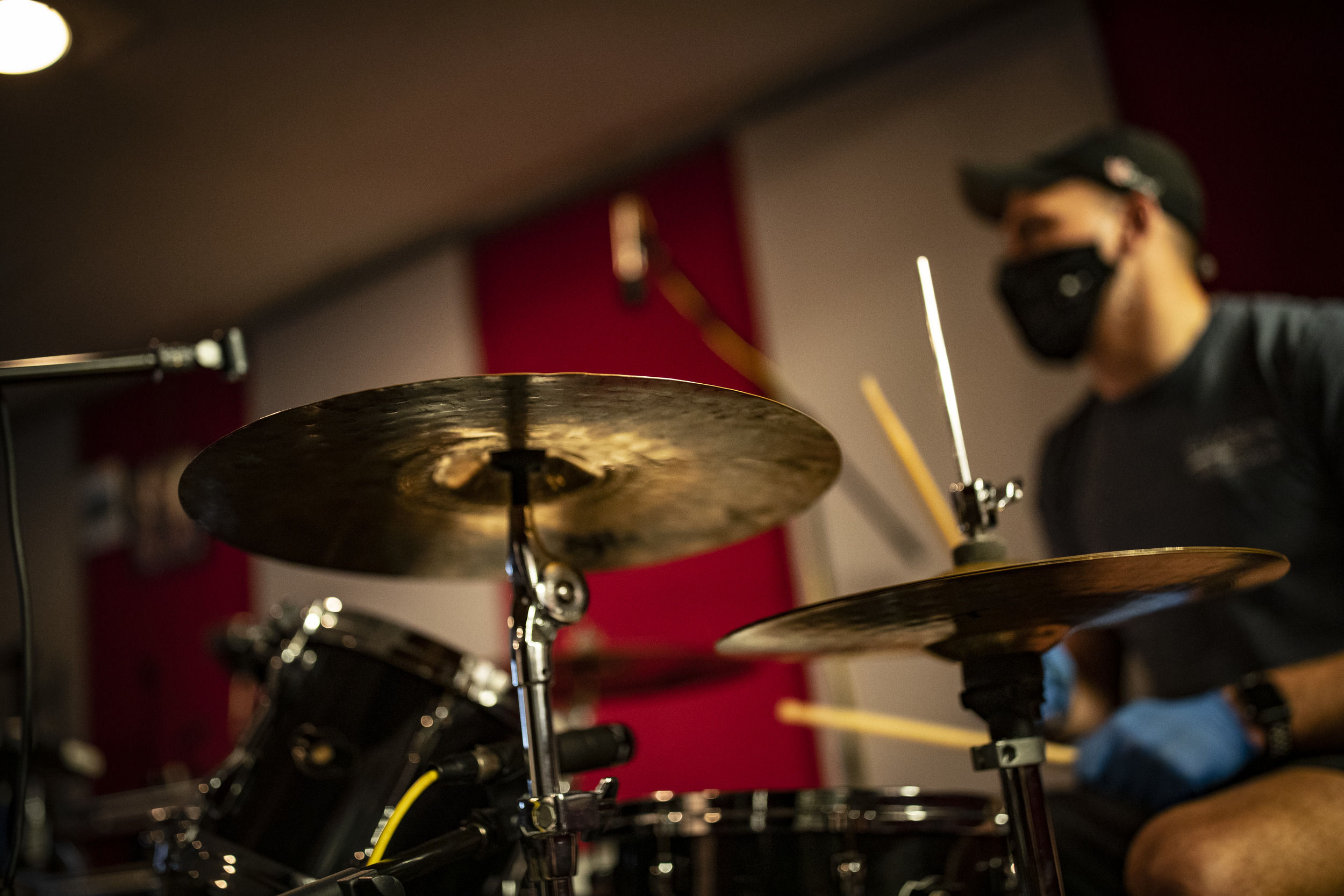 A Klein College of Media and Communications student plays drums during studio music class.