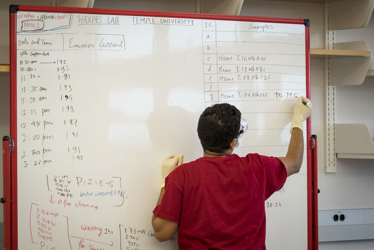 A College of Science and Technology student writes on a white board during physics class.