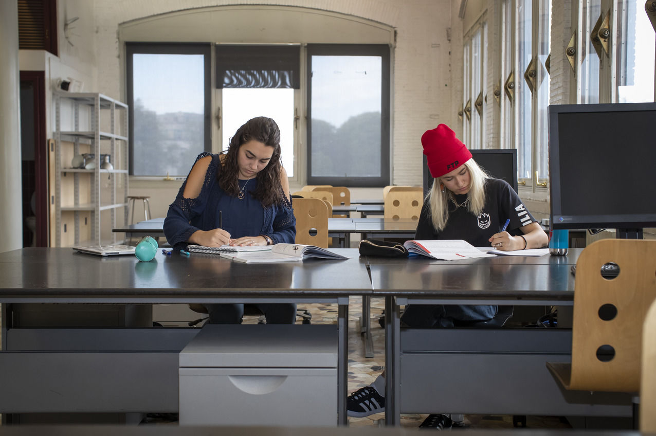 Two students sitting at a table writing in their notebooks in a study space at Temple Rome's campus.