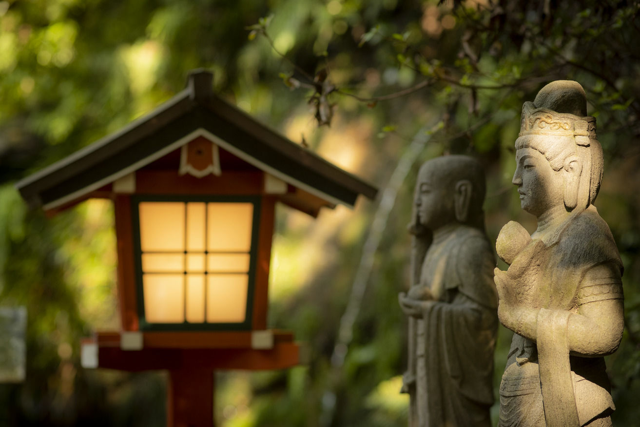 A traditional Japanese lantern and sculptures in a park.