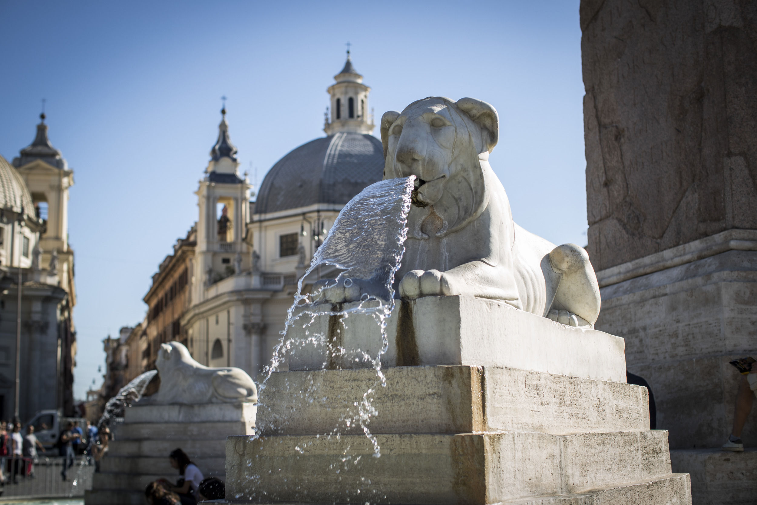 A lion shaped fountain spitting water in central Rome.