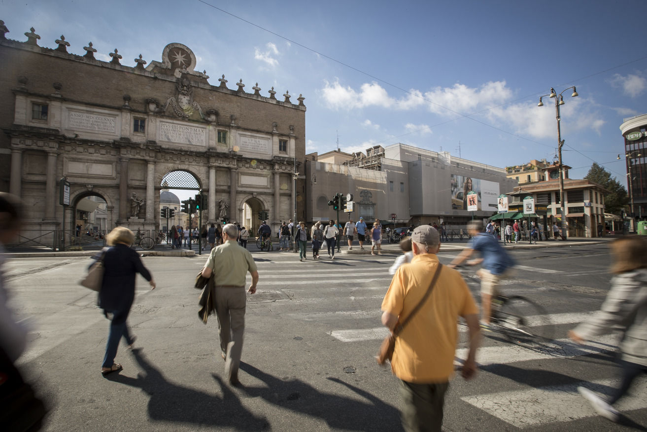 Pedestrians crossing a busy intersection in central Rome.