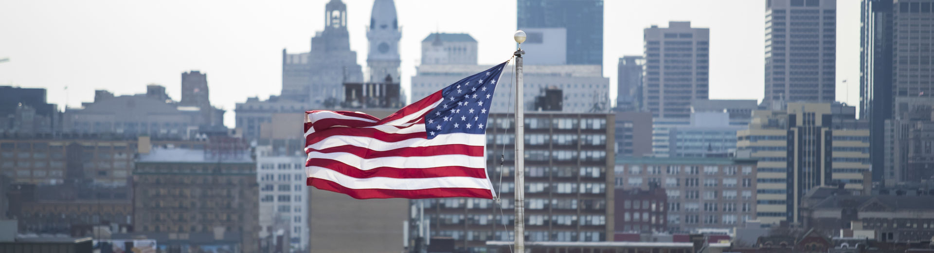 The American flag waves above the Philadelphia city skyline.