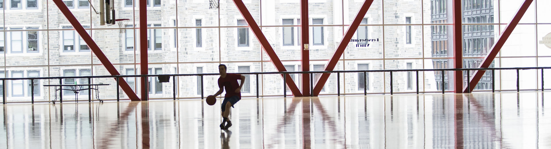 a student practicing basketball alone in the Pearson & McGonigle courts.