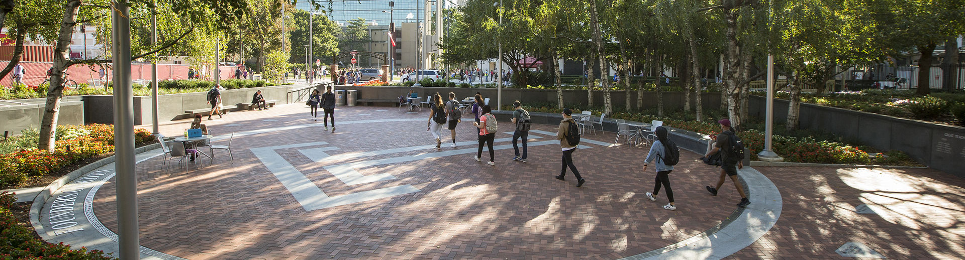 Students walking across campus on a bright sunny day