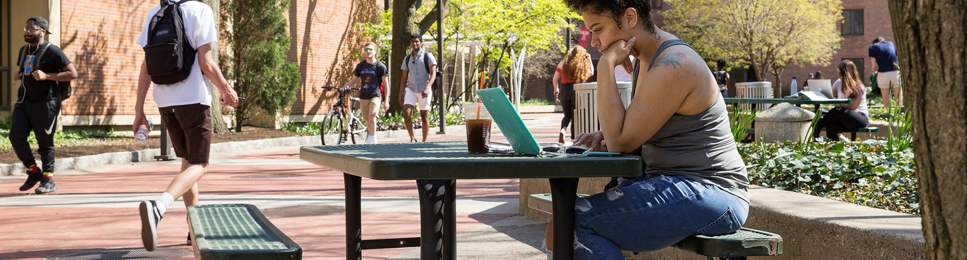 Student working on her laptop seated on a picnic bench in springtime