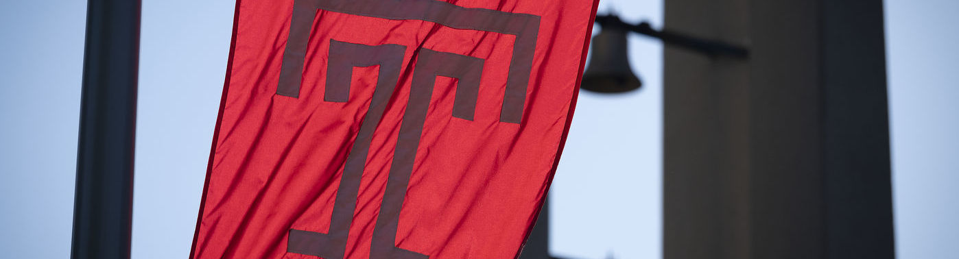 The cherry red Temple T flag waves in front of the bell tower on Main Campus.